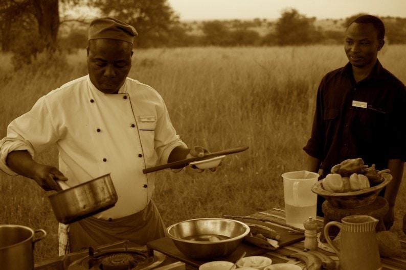 Fredy of Sayari Camp  bereitet die Green Banana Soup vor.
