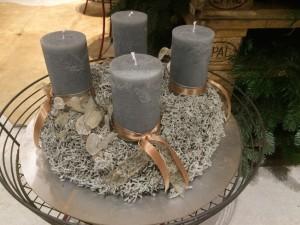 Graue Kerzen und einen Kranz aus getrocknetem Moos.